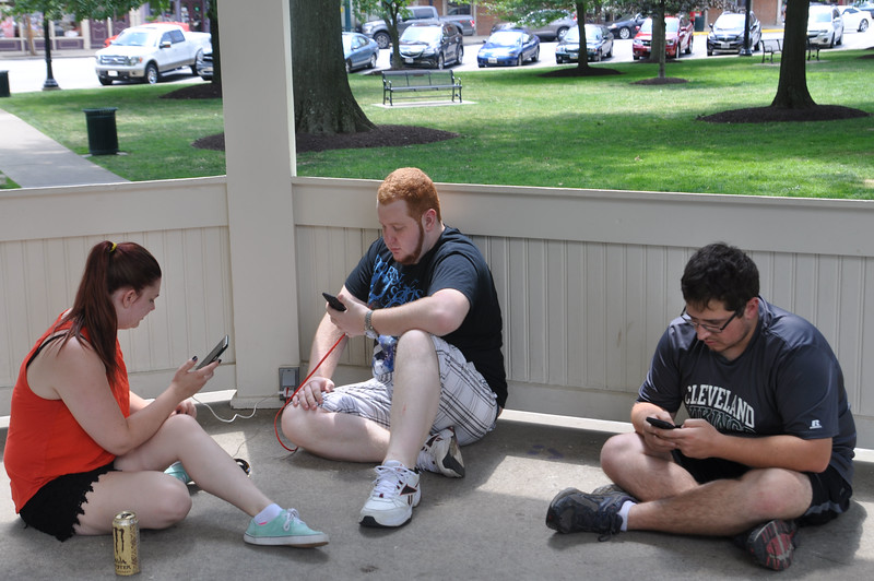 ASHLEY FOX / GAZETTE Left to right, Christina Heishman, Todd Smith, both 21 and from Medina, and Jacob Albright, 25 and from North Royalton, charge up their phones as they play Pokémon Go on Monday afternoon. Heishman and Smith met Albright through the game.