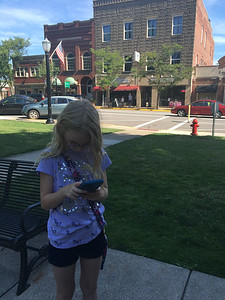 ASHLEY FOX / GAZETTE Elaine Steel, 11, of North Royalton, ended up at the gazebo in Medina on Monday with her brother Henry, 7, and their mother, Julie, while playing Pokémon Go. The game has become a sensation since launching on July 6. The Steels have visited three metro parks and various areas because of the game.