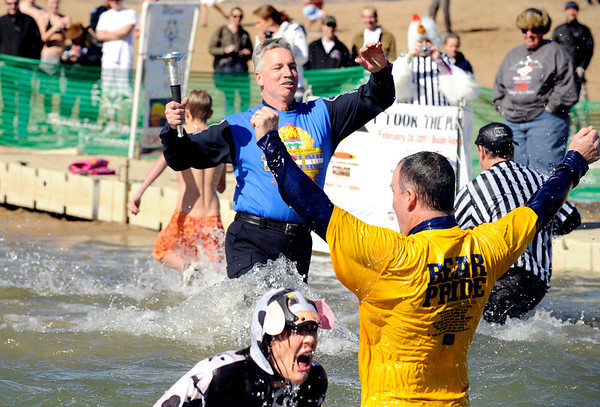 Boulder Police sergeant Dave Seper, blue shirt, runs the torch into the frigid water on Saturday, Feb. 26, during the Law Enforcement Torch Run Polar Plunge for Colorado Special Olympics at the Boulder Reservoir.<br /> Jeremy Papasso/ Camera