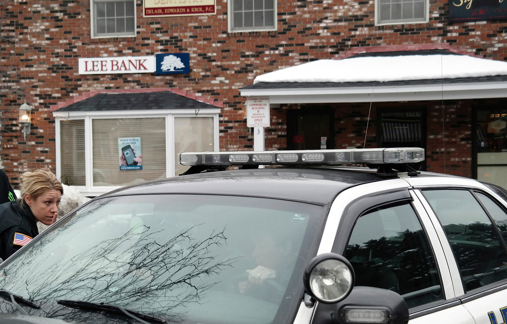 . Stockbridge police officer Heidi Teusch talks with another officer in a squad car at the scene of the Lee Bank branch on Elm Street in Stockbridge. Police were investigating an alleged robbery that took place there Monday afternoon. Ben Garver/Berkshire Eagle Staff Monday, March 10, 2014