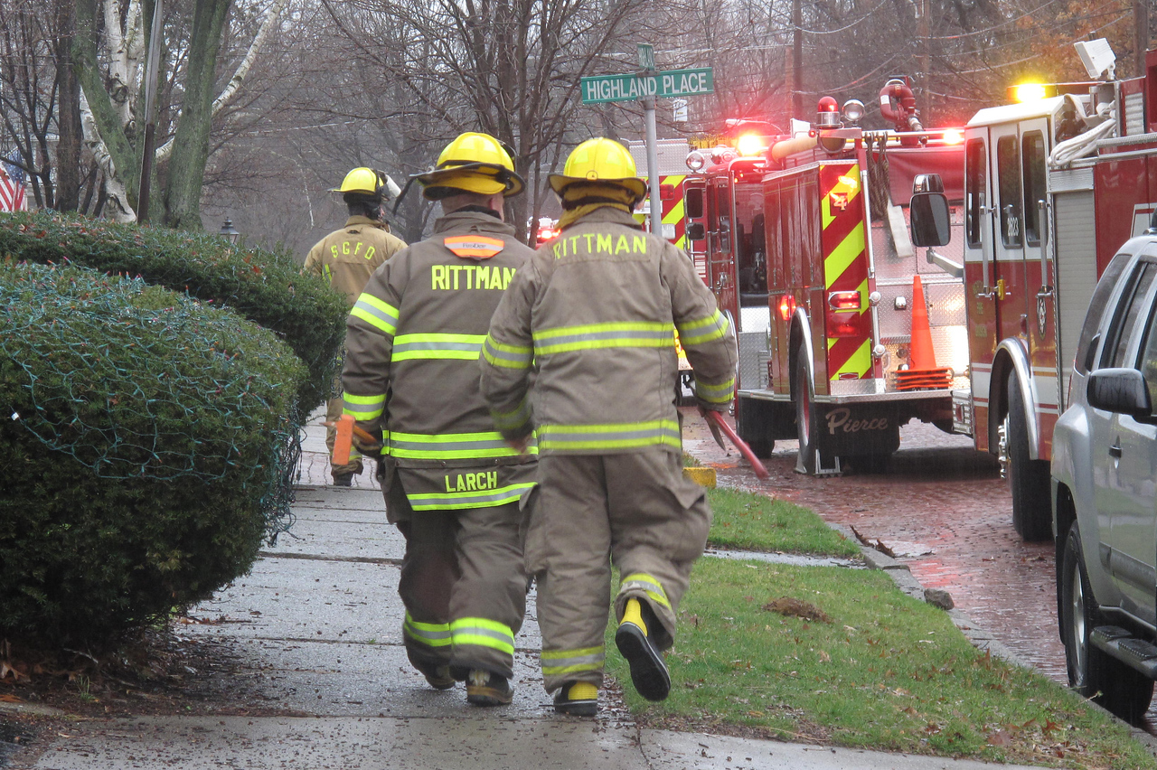 KATIE ANDERSON / GAZETTE Two Rittman firefighters walk down Highland Avenue in Wadsworth to the scene of a house fire Sunday afternoon at 162 Highland Ave.
