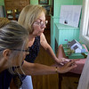 ELODIE REED - FOR THE BENNINGTON BANNER Pownal resident Carol Shuey, right, and Pownal Historical Society board member Pauline Guntlow, left, look over the proposed plans for incorporating the 1840's School House #8 into a new town offices structure.