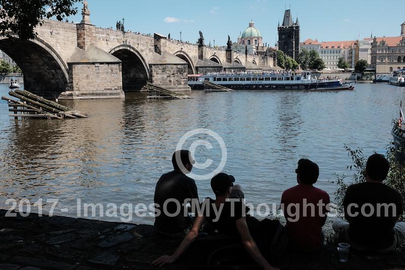 Visitors sit along the left bank (west) of the Vltava River in Mala Strana, Prague.