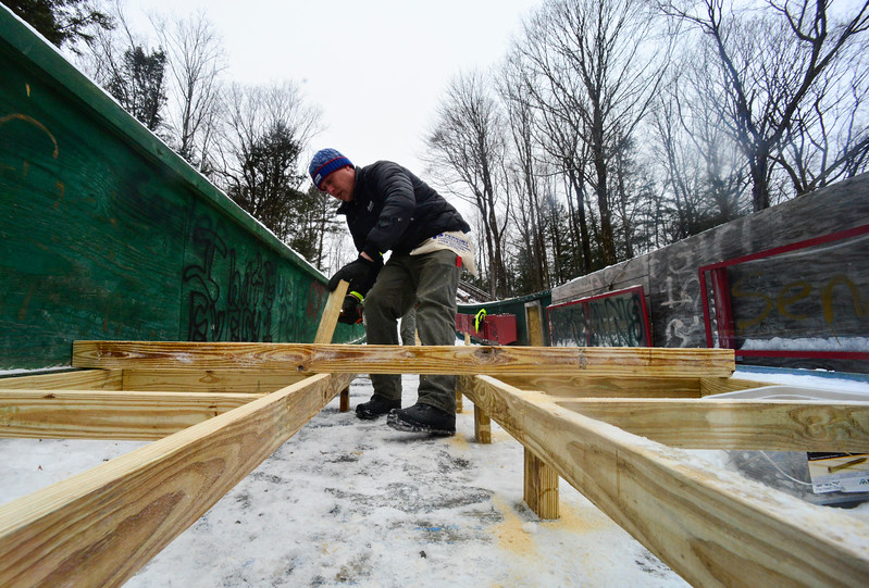 KRISTOPHER RADDER - BRATTLEBORO REFORMER <br /> Drew Christiansen, of Evans Construction, puts footings onto the wood frame that is being used to slim the inrun at the Harris Hill Ski Jump.