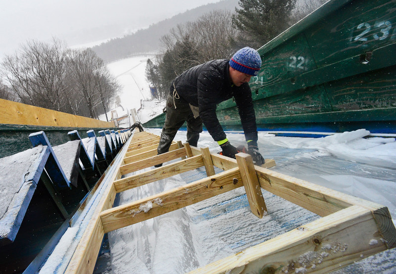 KRISTOPHER RADDER - BRATTLEBORO REFORMER <br /> Drew Christiansen, of Evans Construction,  works on tracking down the tacks at the Harris Hill Ski Jump.