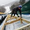 KRISTOPHER RADDER - BRATTLEBORO REFORMER <br /> Drew Christiansen, of Evans Construction, works on tracking down the tacks at the Harris Hill Ski Jump.