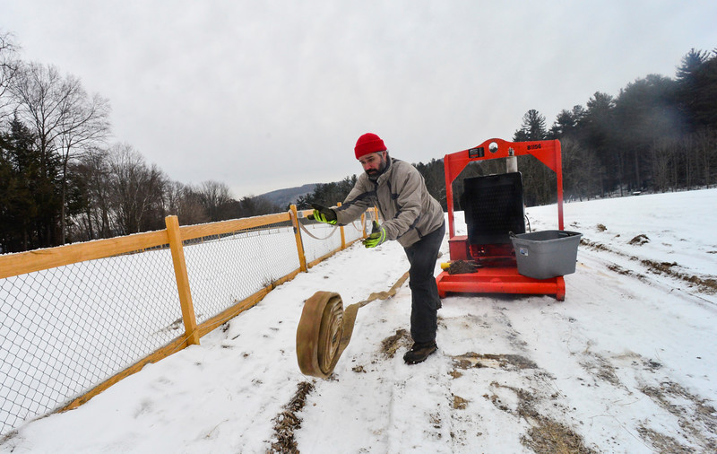 KRISTOPHER RADDER - BRATTLEBORO REFORMER <br /> Glenn Rosinski, of Evans Construction, rolls out hoses for the snowmakers before they blow snow at the Harris Hill Ski Jump on Wednesday, Feb. 7, 2018.