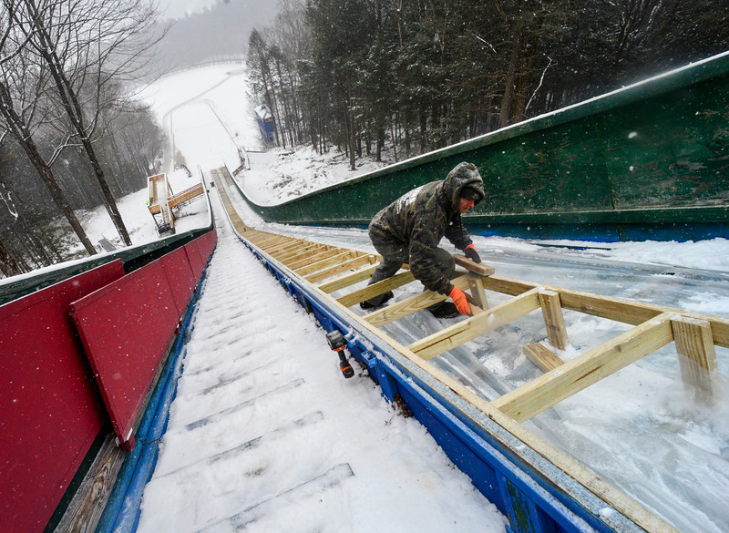 KRISTOPHER RADDER - BRATTLEBORO REFORMER <br /> Jeff Kneeland, of Evans Construction, works on tracking down the tack at the Harris Hill Ski Jump.