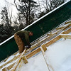 KRISTOPHER RADDER - BRATTLEBORO REFORMER <br /> Drew Christiansen, of Evans Construction, drills in the new wood frame for the inrun at the Harris Hill Ski Jump.