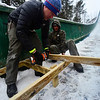 KRISTOPHER RADDER - BRATTLEBORO REFORMER <br /> Drew Christiansen, of Evans Construction, drills in the footings while Jeff Kneeland holds the wood frame.