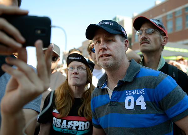 Steve O'Halloran, center, of Boulder, watches the finish of the USA Pro Cycling Challenge being broadcast on a smart phone along with Pam Daniel, left, and her husband Henry Daniel, right, while they were on Pearl Street in Boulder Saturday Aug. 25, 2012. (Lewis Geyer/Boulder Daily-Camera)