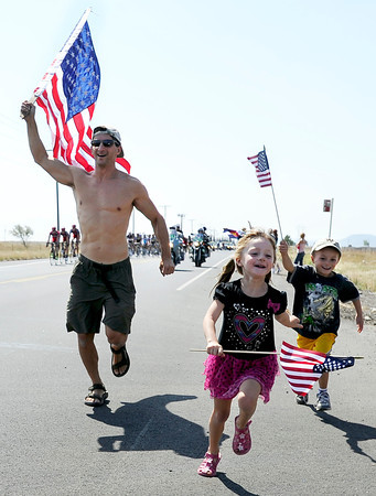 "Alan Villavicencio, left, his daughter Tori, 5, and son Vinko, 6, run with American flags in front of the Peloton during Stage 6 of the USA Pro Challenge on Saturday, Aug. 25. For more photos and video of the race go to  <a href=""http://www.dailycamera.com"">http://www.dailycamera.com</a><br /> Jeremy Papasso/ Camera"