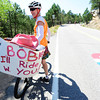 Jenette Settle with her sign hoping to ride with announcer Bob Roll is shock after the former rider just rode by and said hello on Flagstaff Mountain the finishing climb of the Pro Cycling Challenge in Boulder.<br /> Photo by Paul Aiken