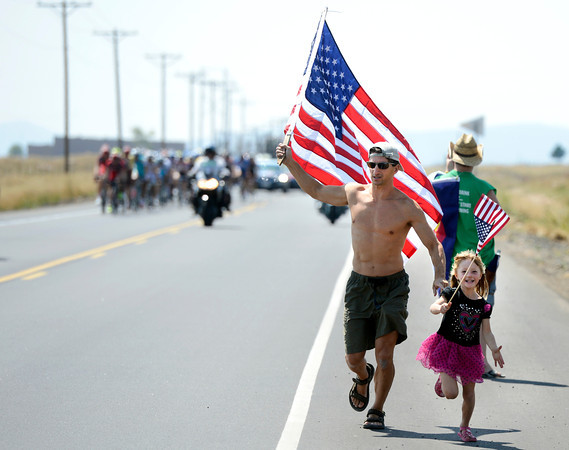 "Alan Villavicencio and his daughter Tori, 5, run in front of the Peloton during the USA Pro Challenge on Saturday, Aug. 25. For more photos and video of the race go to  <a href=""http://www.dailycamera.com"">http://www.dailycamera.com</a><br /> Jeremy Papasso/ Camera"