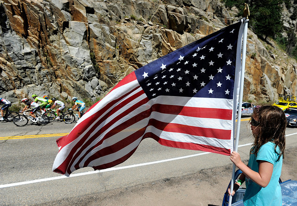 "Kaitlyn Sullivan, 6, of Boulder, stands on the roof of a van holding an American flag as the peloton passes by during a section of Stage 6 of the USA Pro Challenge on Saturday, Aug. 25. For more photos and video of the race go to  <a href=""http://www.dailycamera.com"">http://www.dailycamera.com</a><br /> Jeremy Papasso/ Camera"