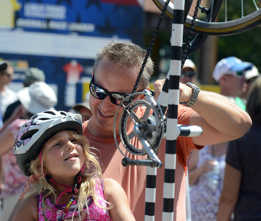 Greg Fowler, of Boulder, helps his daughter Sophia, 6, spin a stationary bicycle contraption on Pearl Street during the USA Pro Cycling Challenge in Boulder Saturday Aug. 25, 2012. (Lewis Geyer/Boulder Daily-Camera)