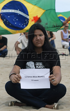 A human rights activist hold the name of one of 12 childen killed in a school shooting, during a protest against the sale of guns in Copacabana beach, Rio de Janeiro, Brazil, April 10, 2011.  A gunman opened fire in an elementary school in Rio de Janeiro and at least 13 people are dead, including the gunman. (Austral Foto/Renzo Gostoli)