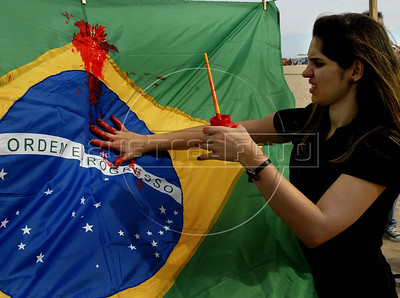 Human rights activists paint a Brazilian flag painted in fake blood,  during a protest against sale of guns in Copacabana beach, Rio de Janeiro, Brazil, April 10, 2011.  A gunman opened fire in an elementary school in Rio de Janeiro and at least 13 people are dead, including the gunman. (Austral Foto/Renzo Gostoli)