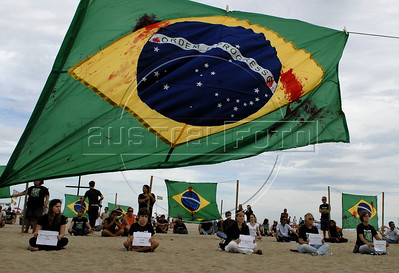 A human rights activist hold the names of the 12 childen killed in a school shooting, during a protest against the sale of guns in Copacabana beach, Rio de Janeiro, Brazil, April 10, 2011.  A gunman opened fire in an elementary school in Rio de Janeiro and at least 13 people are dead, including the gunman. (Austral Foto/Renzo Gostoli)