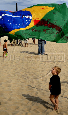 A baby passes by a Brazilian flag painted in fake blood, representing 12 childen killed in a school shooting, during a protest against the sale of guns in Copacabana beach, Rio de Janeiro, Brazil, April 10, 2011.  A gunman opened fire in an elementary school in Rio de Janeiro and at least 13 people are dead, including the gunman. (Austral Foto/Renzo Gostoli)