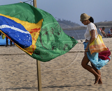 A woman passes by a Brazilian flag painted in fake blood, representing 12 childen killed in a school shooting, during a protest against the sale of guns in Copacabana beach, Rio de Janeiro, Brazil, April 10, 2011.  A gunman opened fire in an elementary school in Rio de Janeiro and at least 13 people are dead, including the gunman. (Austral Foto/Renzo Gostoli)