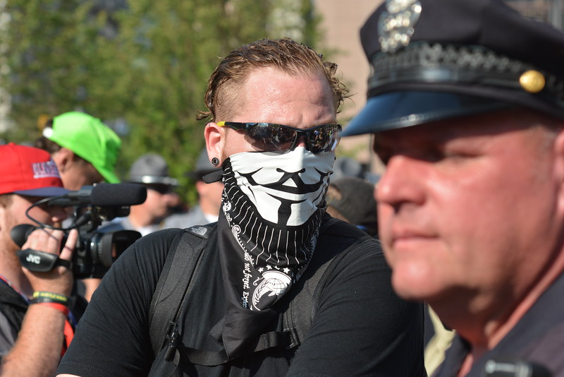 BILL KEATON/GAZETTE An anarchist makes his way through Public Square in Cleveland on Tuesday.