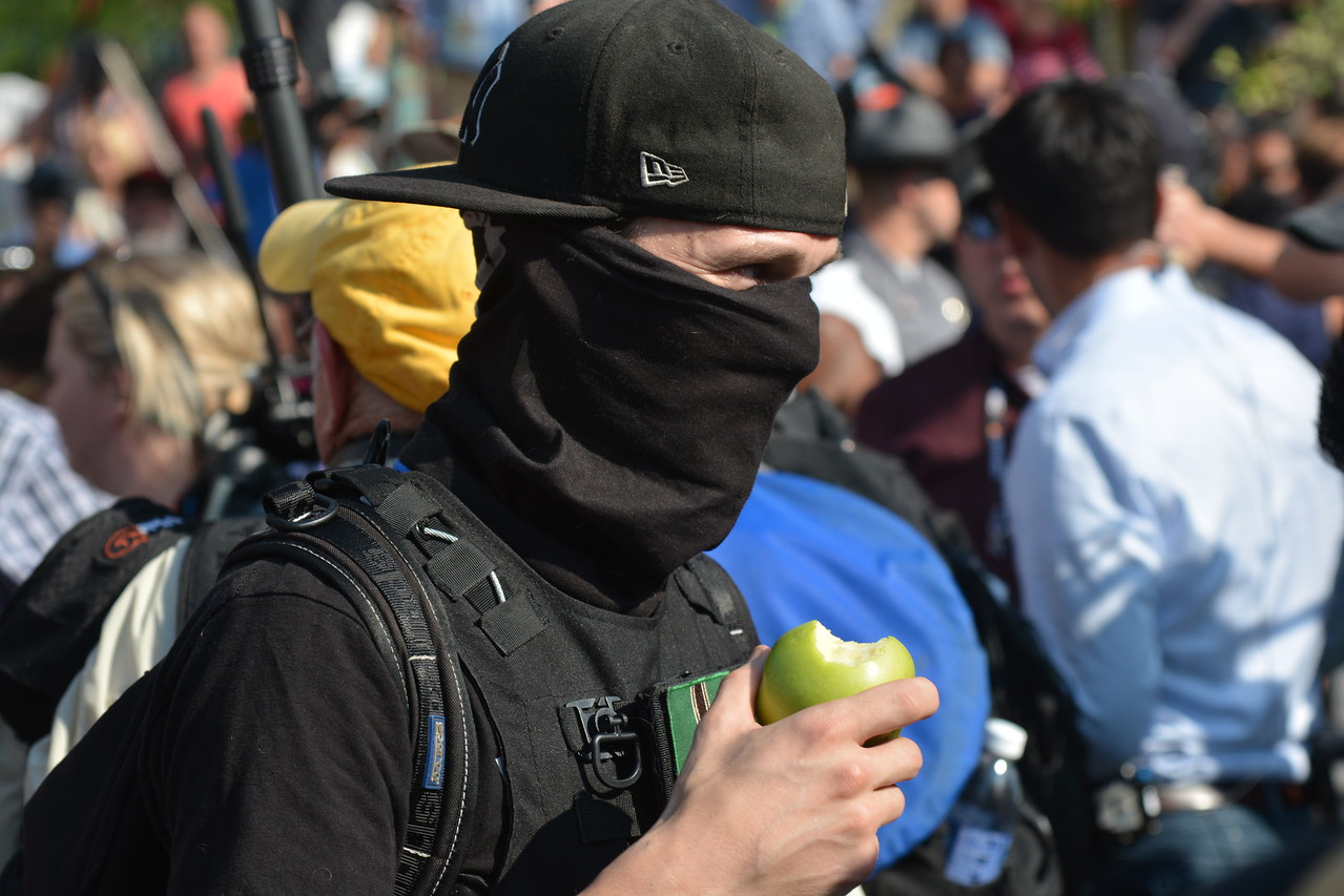 BILL KEATON/GAZETTE A protester eats an apple in downtown Cleveland on Tuesday, July 19.