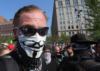 BRUCE BISHOP/GAZETTE An anarchist makes his way through Public Square in Cleveland on Tuesday.