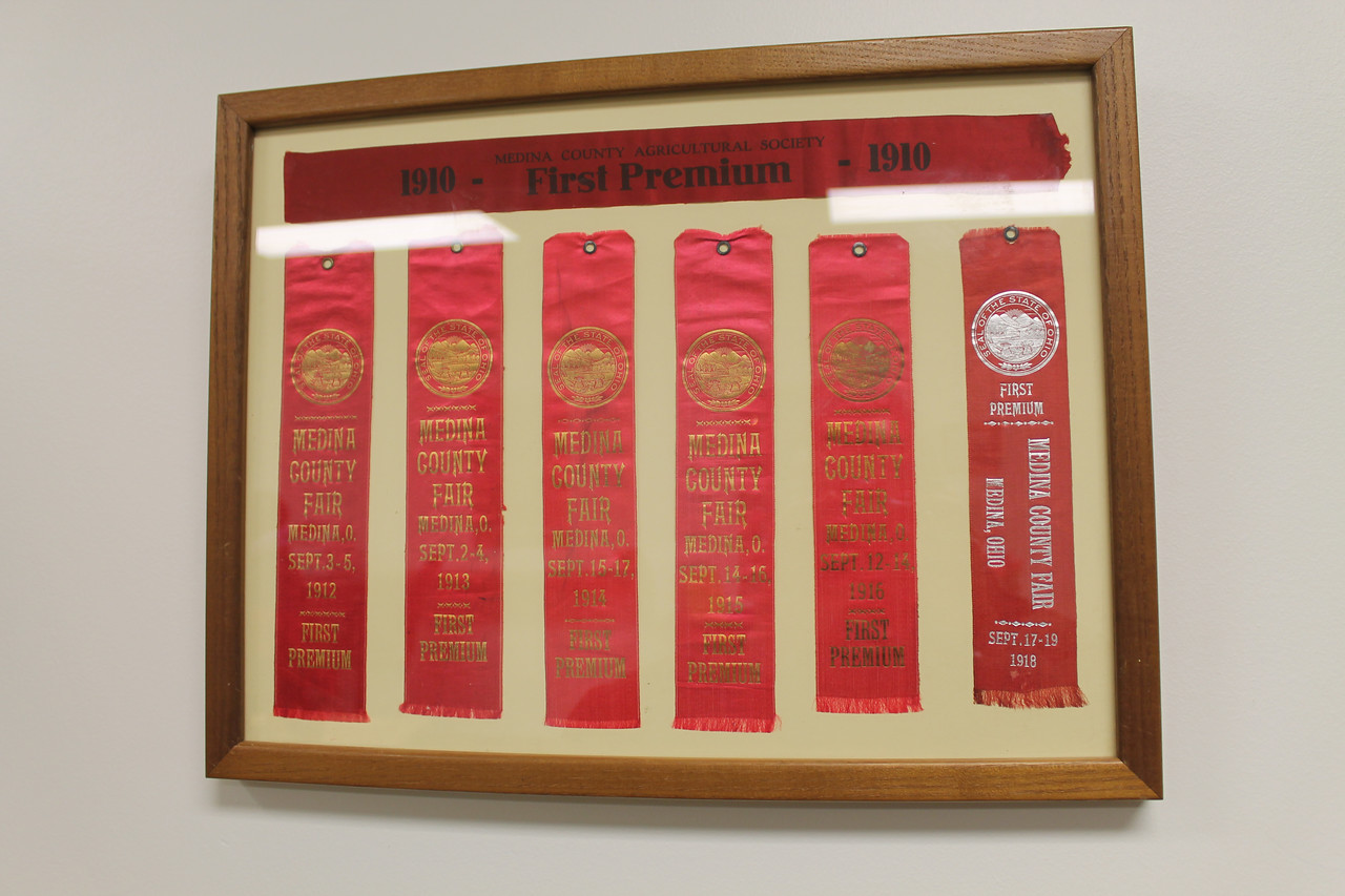 LAWRENCE PANTAGES / GAZETTE A framed display of red ribbons dating to the early 1900s is included in wall decorations at the new Medina County Fair Board building.