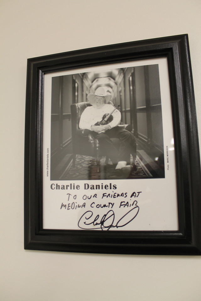 LAWRENCE PANTAGES / GAZETTE  An autographed photo of Charlie Daniels is among photos hanging in an office area of the new Medina Fair Board building that was opened to the public Wednesday night.