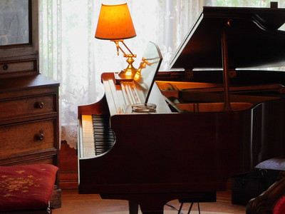 A grand piano sits in the front room of the McDowell-Phillips house. One of seven fireplaces is in this room. A pianist was playing during the open house Thursday evening. BOB FINNAN / GAZETTE