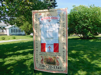 BOB FINNAN / GAZETTE A sign in the front yard of the McDowell-Phillips House shows the progress toward the goal of raising $500,000 for the purchase and renovation of the house built in 1890.