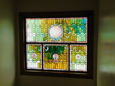A stained-glass window sits above the staircase leading up to the second floor at the McDowell-Phillips home. BOB FINNAN / GAZETTE
