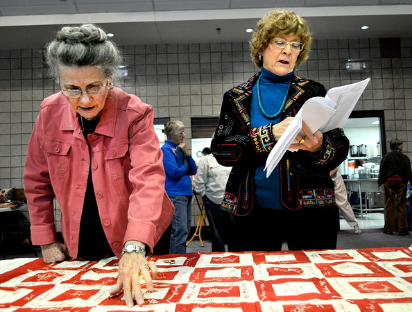 "Bonnie Swanson, left, points out a name on a quilt that Jane Haeker reads off of from her information sheet at First Lutheran Church in Longmont on Monday Feb. 11, 2013. The quilt was made in 1895, and was recently found in the church's vault. DAILY CAMERA/ JESSICA CUNEO. For more photos and a video, go to <a href=""http://www.timescall.com/"">http://www.timescall.com/</a>."