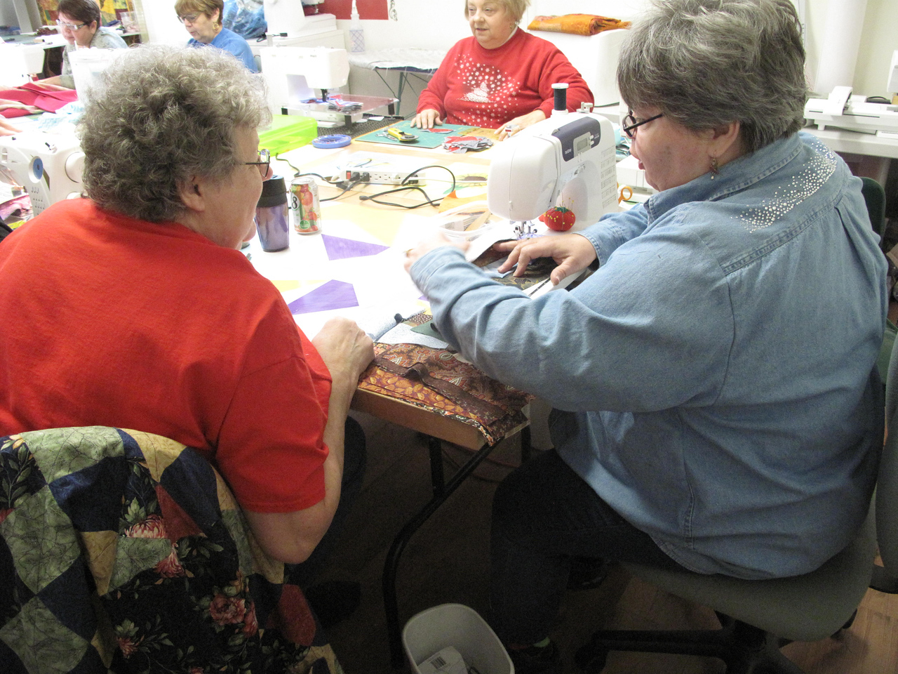 ELIZABETH DOBBINS / THE GAZETTE Jan Codney and Ruth Sopata chat while they work on projects at the Little Red Quilt House.