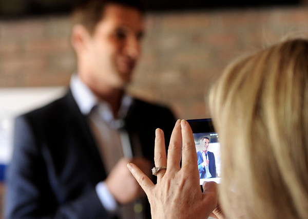 "Kathy Phillips, of Boulder, takes an Iphone photograph of Josh Romney's speech during a Mitt Romney campaign stop on Thursday, Sept. 13, at Geisty's Dogg House in Boulder. For a video of the Romney campaign stop go to  <a href=""http://www.dailycamera.com"">http://www.dailycamera.com</a><br /> Jeremy Papasso/ Camera"