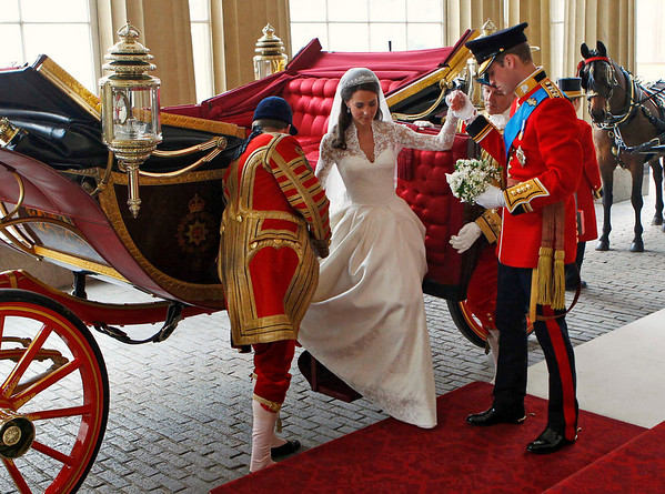 Britain's Prince William, right, helps his wife Kate, the Duchess of Cambridge, down the steps of the 1902 State Landau carriage as they arrive at Buckingham Palace after their wedding at Westminster Abbey, London, Friday, April 29, 2011. (AP Photo/Andrew Winning, Pool)