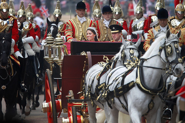 Prince William and his wife Kate, the Duchess of Cambridge make their way in an open carriage along The Mall, London from Westminster Abbey to Buckingham Palace after their wedding Friday April 29, 2011. (AP Photo/James Glossop, Pool)