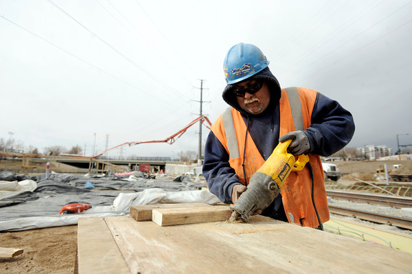 "Mesa Construction's Juan Valdez uses a jigsaw to cut footer boards for concrete while working on RTD's West Line Lightrail track at 13th and Federal in Denver on Thursday, March 1. For more photos and video of the construction go to  <a href=""http://www.dailycamera.com"">http://www.dailycamera.com</a><br /> Jeremy Papasso/ Camera"