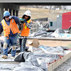 "Mesa Construction's Juan valdez, left, and Marco Antonio-Lucero help each other carry a compacter while working on RTD's West Line Lightrail track at 13th and Federal in Denver on Thursday, March 1. For more photos and video of the construction go to  <a href=""http://www.dailycamera.com"">http://www.dailycamera.com</a><br /> Jeremy Papasso/ Camera"