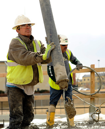 "Mesa Construction's Francisco Rogel, front, pours concrete while working on RTD's West Line Lightrail track at 13th and Federal in Denver on Thursday, March 1. For more photos and video of the construction go to  <a href=""http://www.dailycamera.com"">http://www.dailycamera.com</a><br /> Jeremy Papasso/ Camera"
