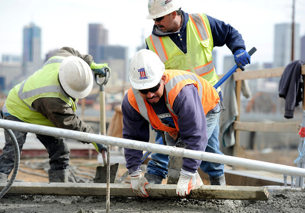 "Mesa Construction's Jesus Ibarra, front, floats some concrete while working on RTD's West Line Lightrail track at 13th and Federal in Denver on Thursday, March 1. For more photos and video of the construction go to  <a href=""http://www.dailycamera.com"">http://www.dailycamera.com</a><br /> Jeremy Papasso/ Camera"