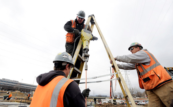 "Lei Conpanie Inc. workers David Martin, top, drives an electrical ground rod while Josh Guzinski, left, and Cory Edens hold the ladder while working on RTD's West Line Lightrail track at 13th and Federal in Denver on Thursday, March 1. For more photos and video of the construction go to  <a href=""http://www.dailycamera.com"">http://www.dailycamera.com</a><br /> Jeremy Papasso/ Camera"