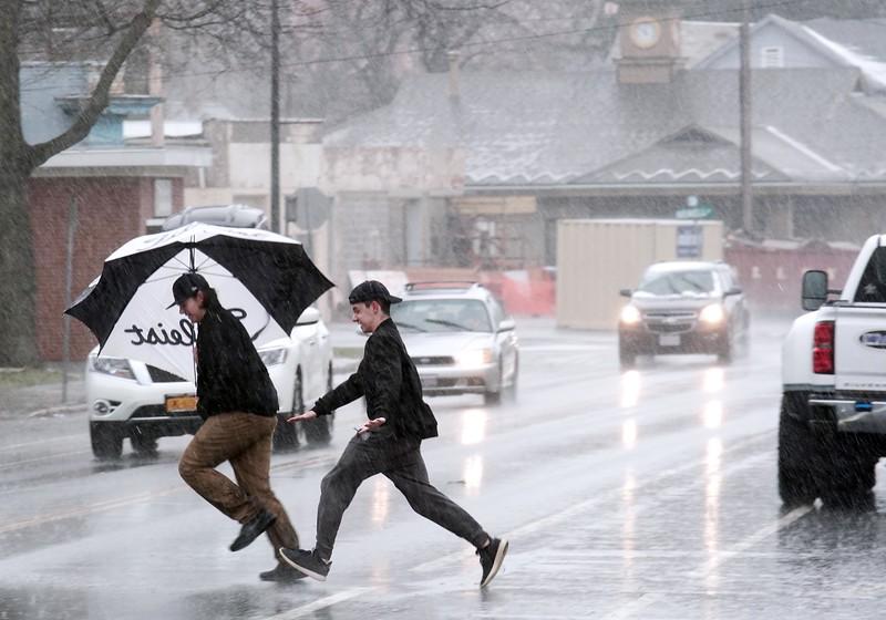 BEN GARVER — THE BERKSHIRE EAGLE<br /> Two boys dash across elm street in heavy rain, Monday, April 16, 2017.