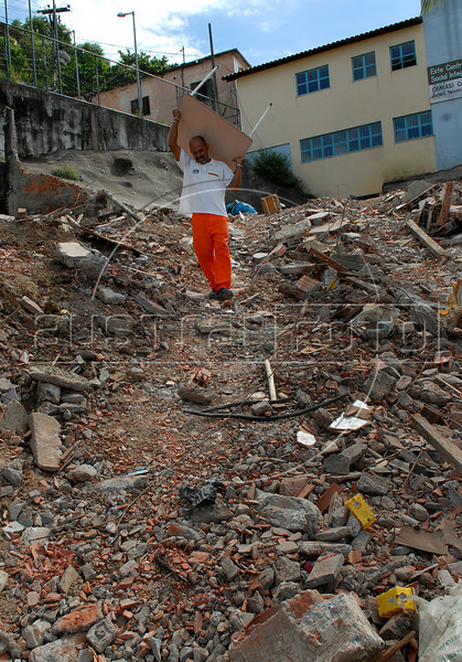 A worker carries goods of an evacuated house, damaged by heavy rains, at the Morro do Urubu slum, Rio de Janeiro, Brazil, April 14, 2010. About 2,600 families are being removed from areas where the threat of new mudslides is most immediate, Rio de Janeiro officials said. The rains of the last week in several cities of Rio de Janeiro state caused at least 50.000 affected and at least 249 deads. (AustralFoto/Renzo Gostoli)