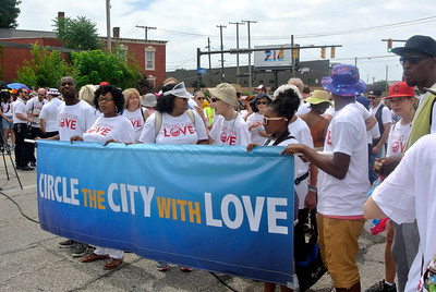 DAVID KNOX / GAZETTE A banner proclaiming Circle the City with Love leads more than 2,000 people crossing the Lorain-Carnegie Bridge in Cleveland Sunday in a protest of violence.