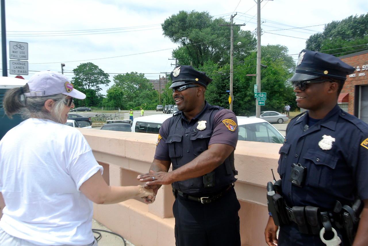 DAVID KNOX / GAZETTE Marci Rich, a graduate of Elyria Catholic and Oberlin College, greets Cleveland police officers providing security for Sunday's Circle the City with Love rally and march.