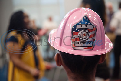 Keziah Williams, 12, wears a pink fire fighters hat at her family's reunion with the Tyler fire fighters who rescued her mom in 1993.