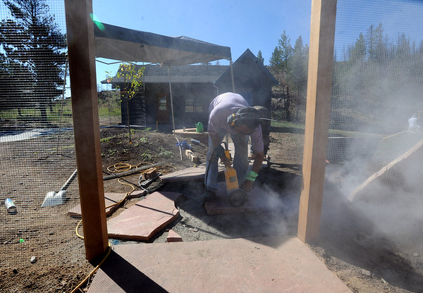 """Cesar Salome cuts up sandstone for the new walkway.<br /> Richard Nuzzi and Stephanie O'Hearn are near completion of rebuilding their home after losing the previous one in the Four Mile Canyon Fire last year.<br /> For a video and more photos from the fire rebuilding, go to  <a href=""""http://www.dailycamer.com"""">http://www.dailycamer.com</a>.<br /> Cliff Grassmick / August 25, 2011"""