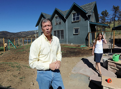 Richard Nuzzi talks about the day his previous home burned to the ground. His wife Stephanie O'Hearn is on the right in front of their new home. Richard Nuzzi and Stephanie O'Hearn are near completion of rebuilding their home after losing the previous one in the Four Mile Canyon Fire last year. For a video and more photos from the fire rebuilding, go to www.dailycamer.com. Cliff Grassmick / August 24, 2011